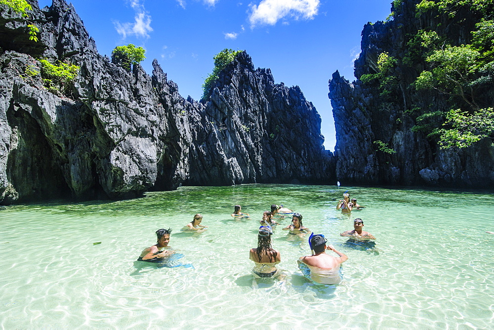 Tourists in the hidden bay with crystal clear water in  the Bacuit archipelago, Palawan, Philippines, Southeast Asia, Asia