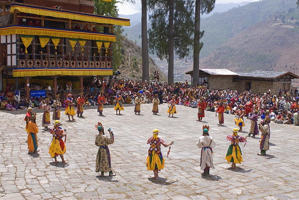 Costumed dancers at religious festival with many visitors, Paro Tsechu, Paro, Bhutan, Asia