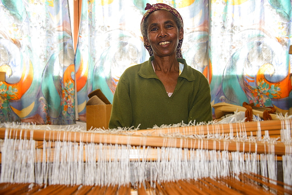 Friendly woman working on a hand weaving loom on a social project in the highlands of Eritrea, Africa