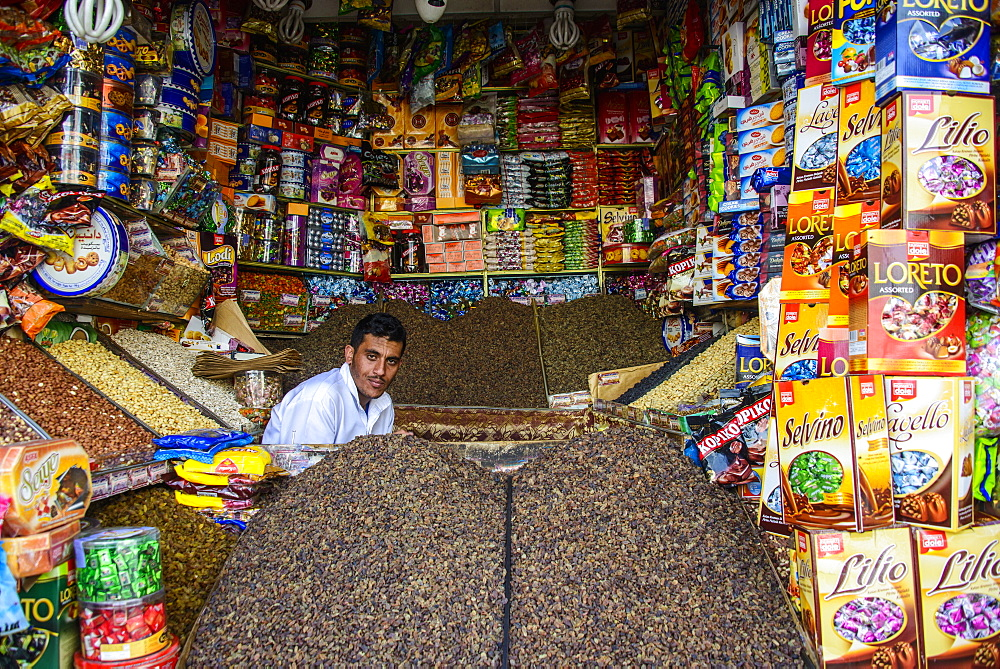 Man sitting in his full shop in the Old Town, UNESCO World Heritage Site, Sanaa, Yemen, Middle East