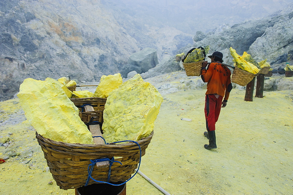 Worker carrying fully loaded baskets of sulphur out of the Ijen Volcano, Java, Indonesia, Southeast Asia, Asia