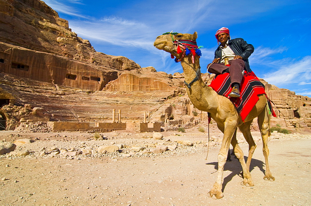 Bedouin on a camel in front of the amphitheater of Petra, UNESCO World Heritage Site, Jordan, Middle East