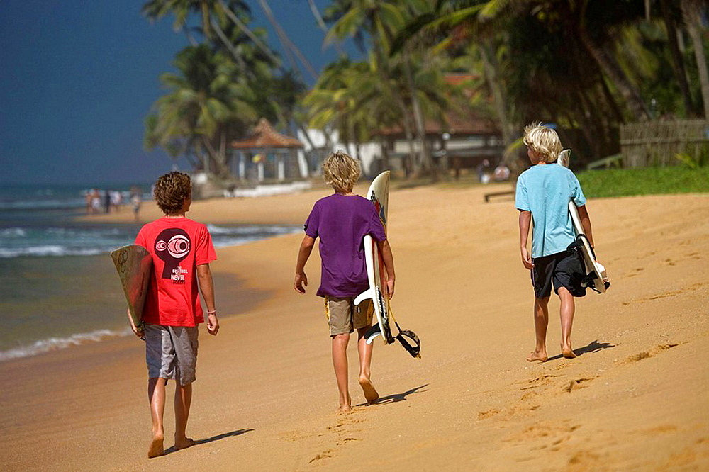 Young surfers walking along Hikkaduwa Beach, Sri Lanka - 817-102744