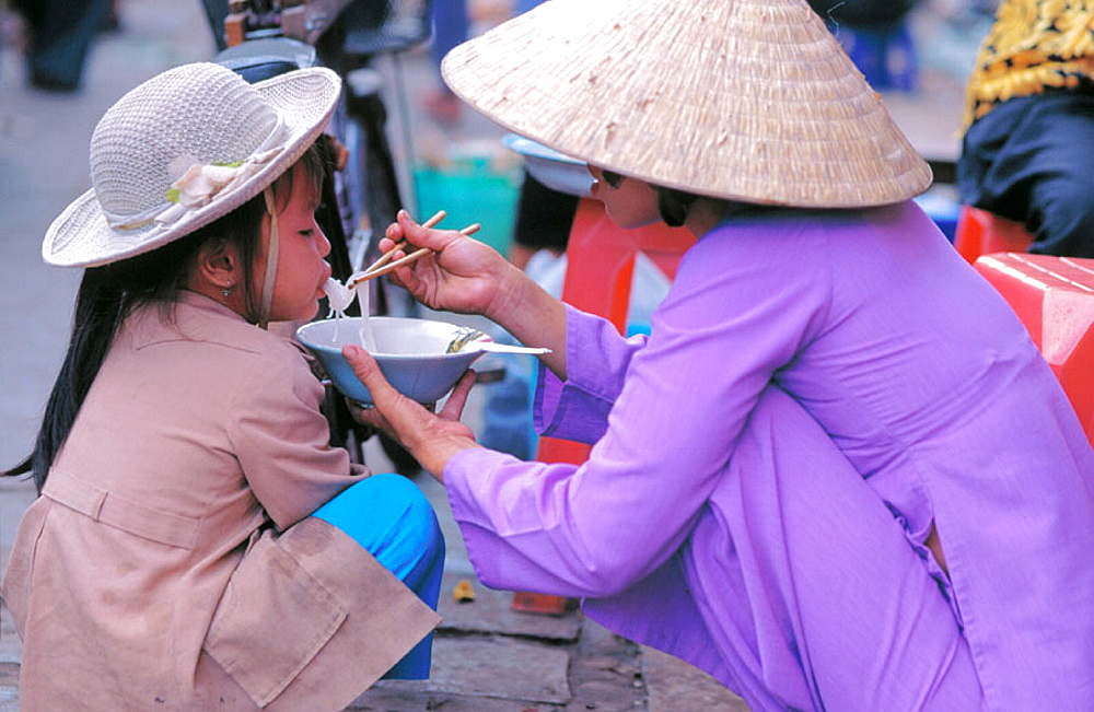 Woman feeding child noodles at market, Hanoi, Vietnam