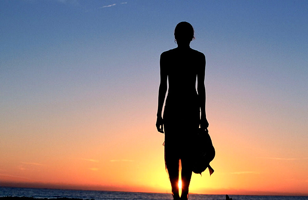 Woman on beach at sunset