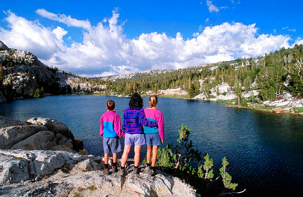 Kids enjoying the view along the shore of Boothe Lake, in the Cathedral Range, Sierra Nevada Mountains, Yosemite NP, California, USA