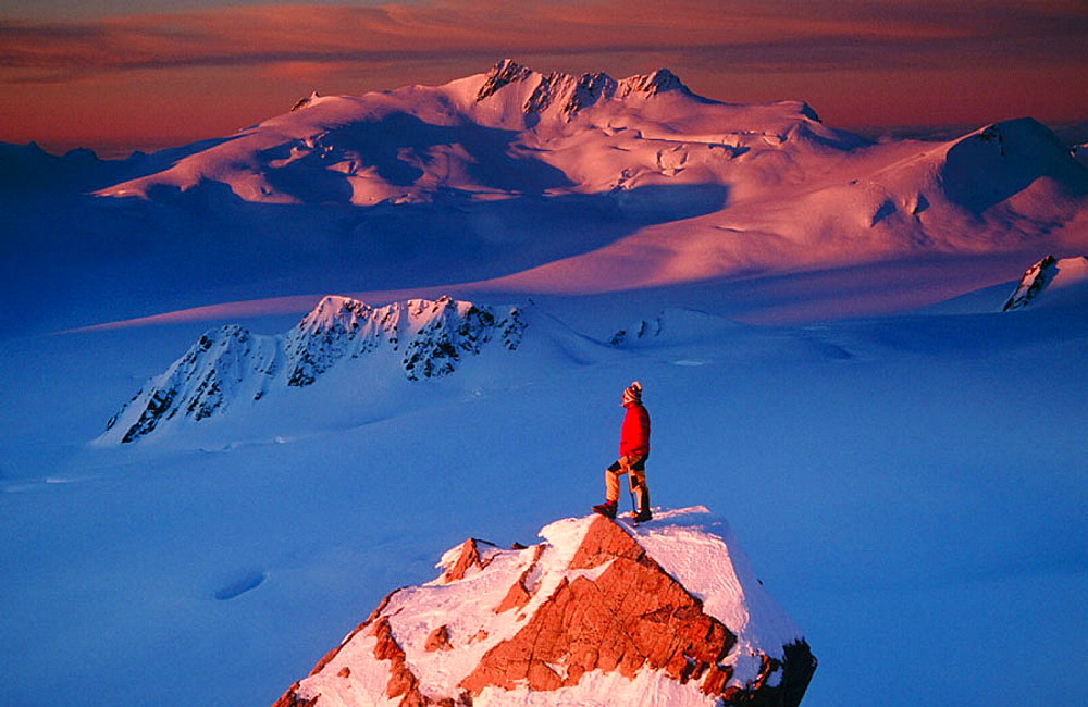 Climber on summit at sunset above Franz Josef Glacier, Westland National Park, New Zealand