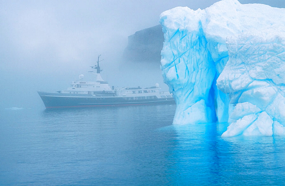 Ship in fog and iceberg off Brown Bluff, Antarctic Peninsula, Antarctica