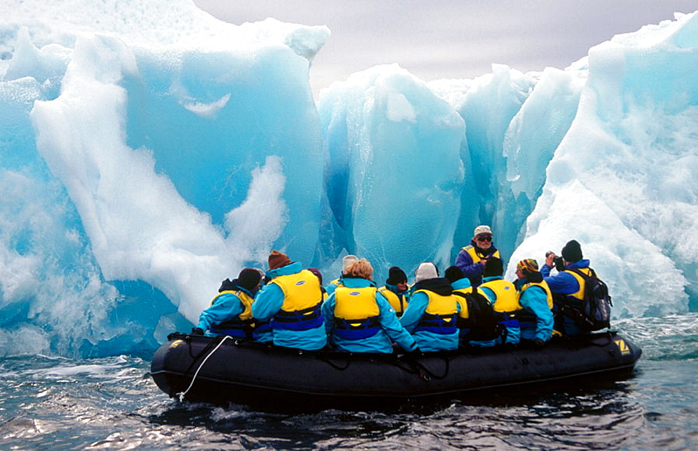 Zodiac with tourists, Past Jade coloured iceberg, Dumont d'Urville, Antarctica