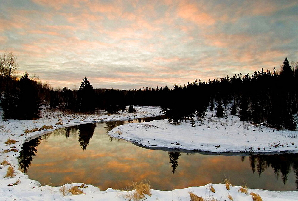 Morning sky reflected in open water of Junction Creek, Ontario, Canada