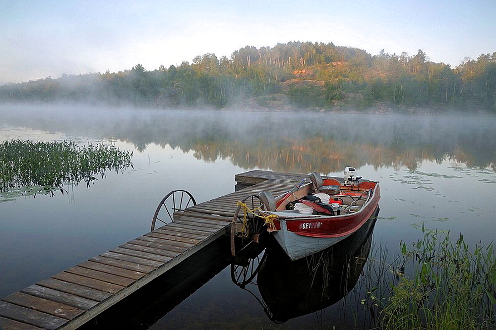 Fishing boat and wharf in morning mists in Elbow Lake