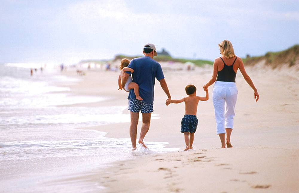 Family on beach, Parents with son and daughter leaving footprints in the sand, nuclear family, Nantucket, Massachusetts,USA