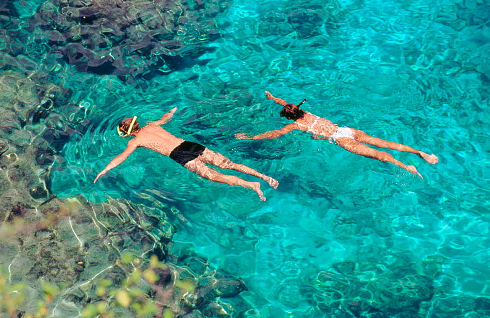 Couple snorkling in cristal clear waters of Curacao