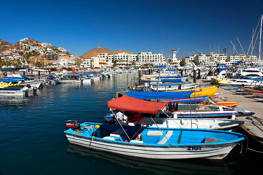 The marina with pleasure boats and a lighthouse at the resort of Cabo San Lucas, Mexico