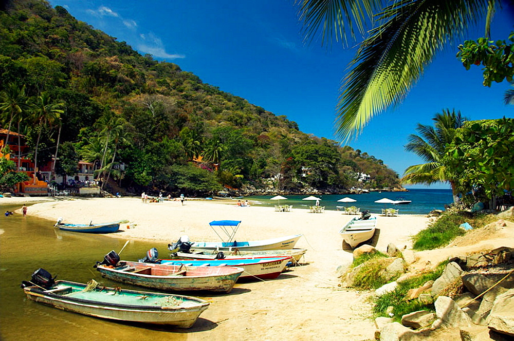 A small sandy beach cove with colorful boats on Banderas Bay south of Puerto Vallarta, Mexico
