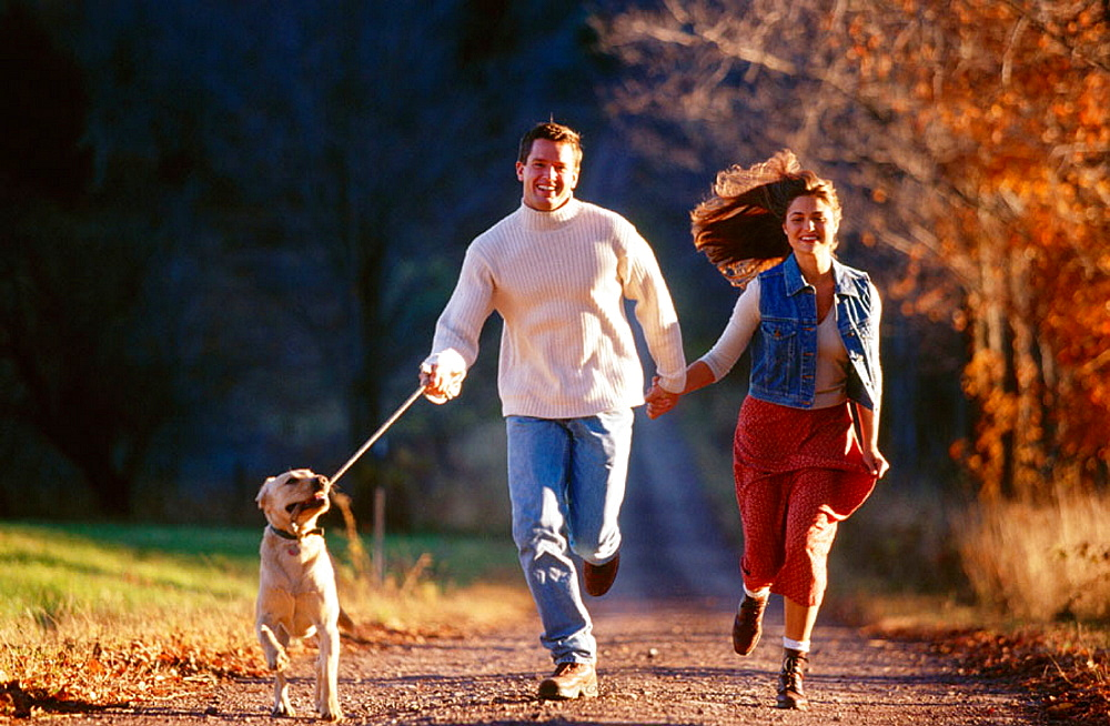 Couple running with their dog on a country road