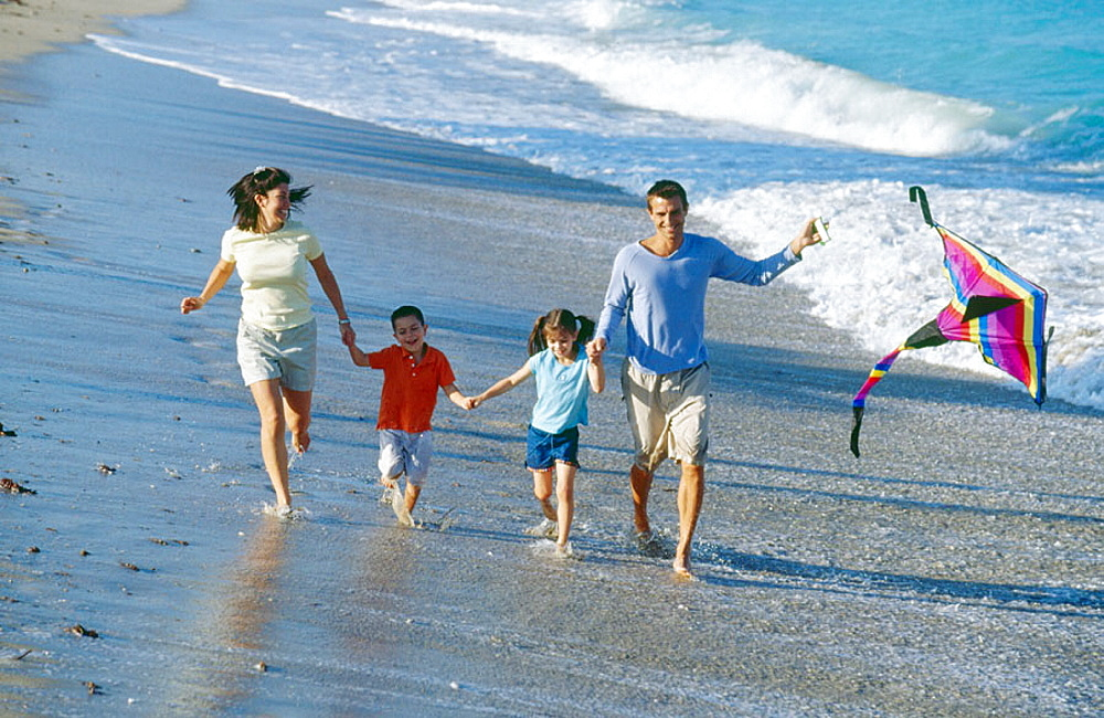 Family of four running along the seashore with a kite