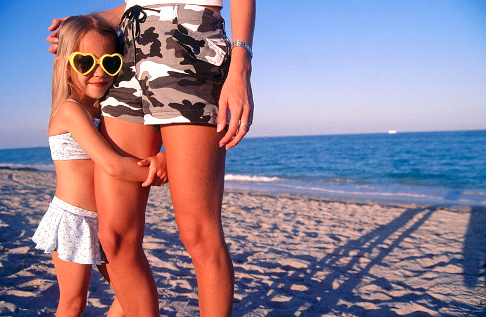 Little girl hugging mom's leg