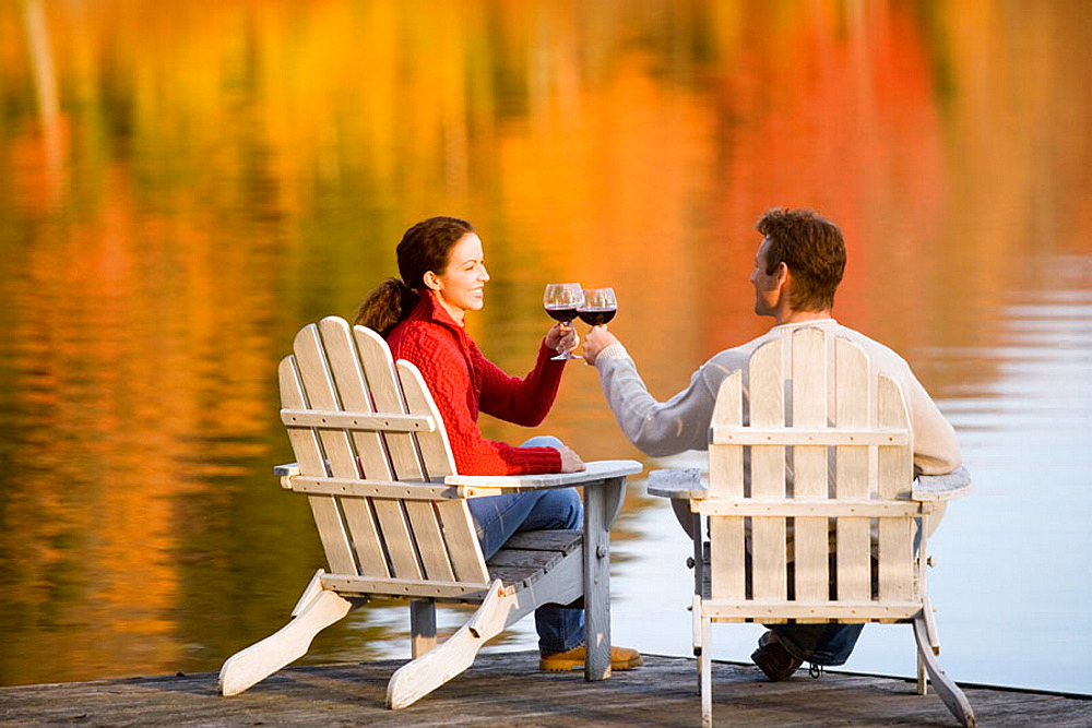 Caucasian couple, age 30's to 40's, wine, adirondack chairs, dock, lake, autumn, reflection