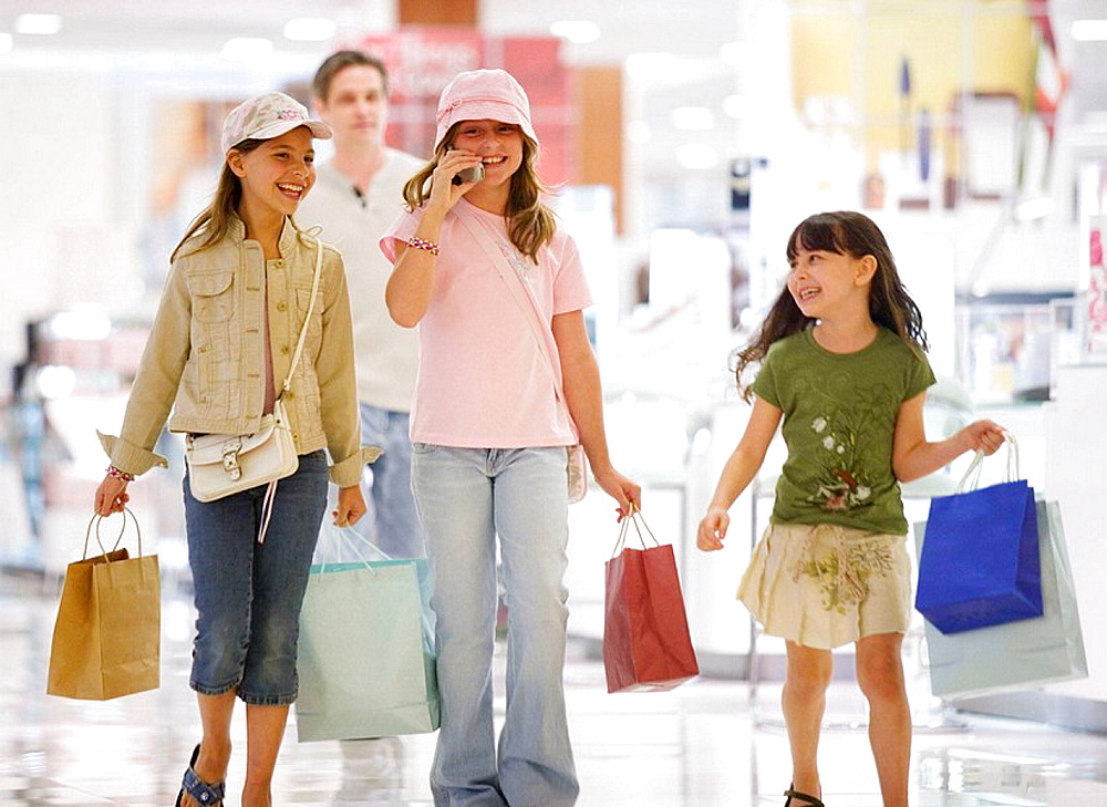 caucasians, hispanic, ages 9 and 10, shopping, talking on cell phone, laughing, smiling, department store, mall, young consumers