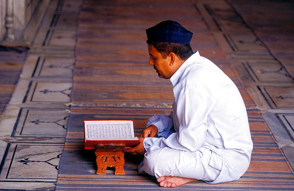 Muslim man reads from the Koran at a the Jama Masjid mosque, Old Delhi, India