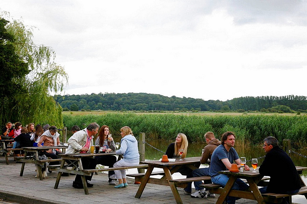 People sitting at the Black Rabbit bar along the river Arun in Arundell,England, UK