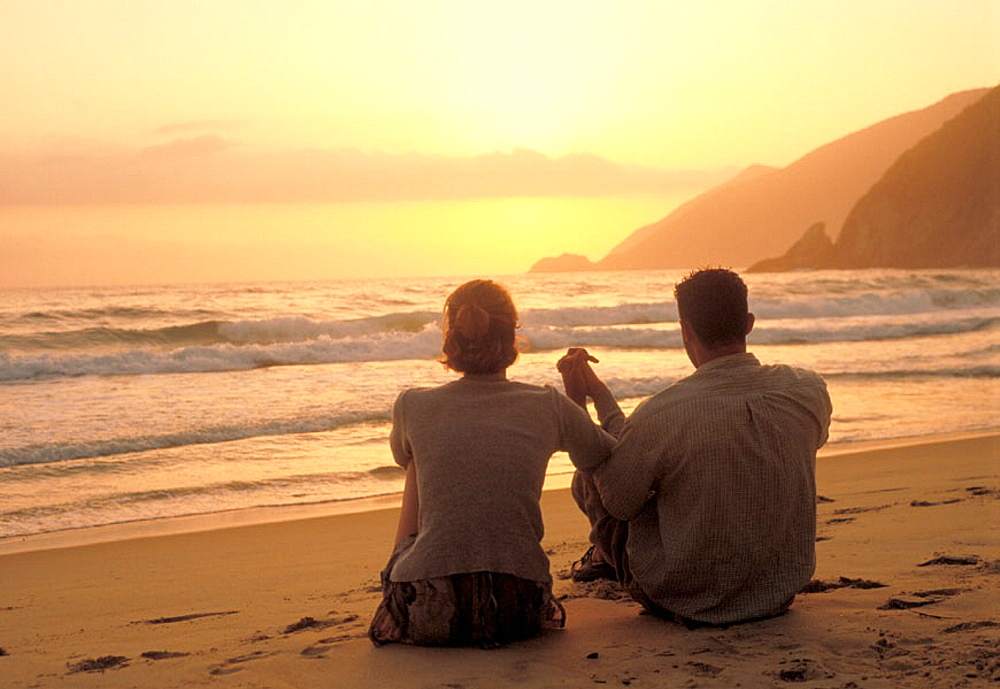 Young couple sitting in the sand holding hands and looking the sunset at the beach, Venezuela