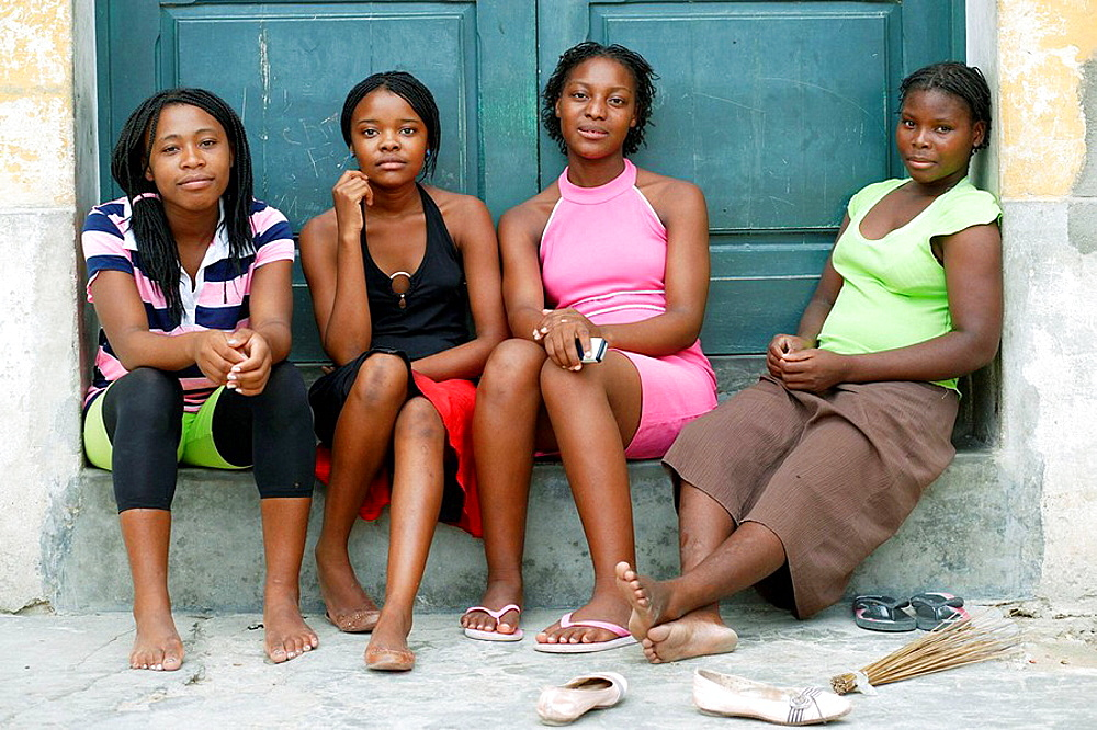 Four young African ladies sitting at a door entrance, Ilha de Mocambique (Island of Mozambique), Mozambique, Southern Africa