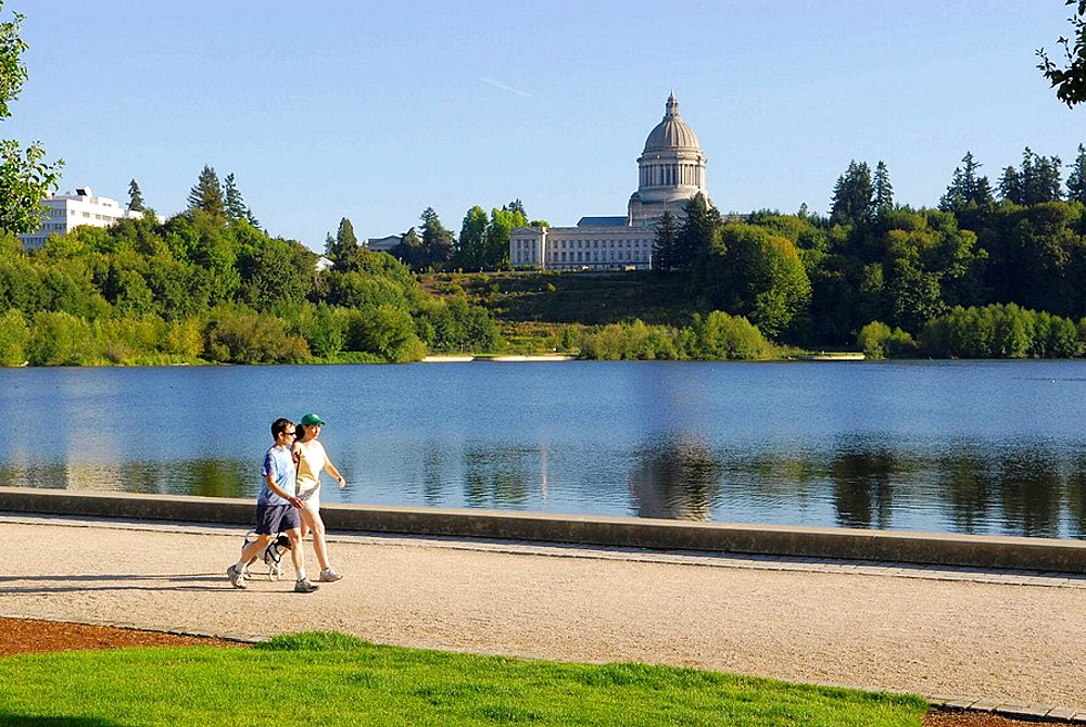 visitors residents walk along Capitol Lake with View of Capitol Building Olympia Washington WA US United States capital legislature legislative laws legal government representatives architects Walter Wilder and Harry White exercise healthy