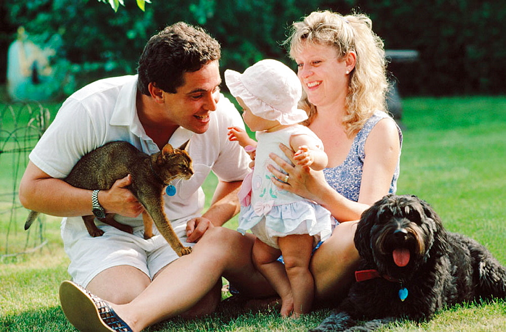 Young couple with baby girl, cat and dog together in back yard