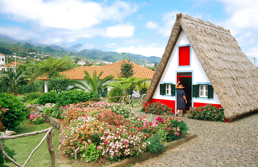 Woman at Palheiro (typical small house), Santana village, Madeira Island, Portugal