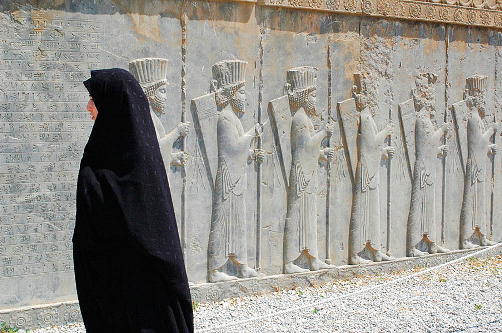 Warriors reliefs and woman in chador, Persepolis (Takht-e Jamshid), Fars, Iran