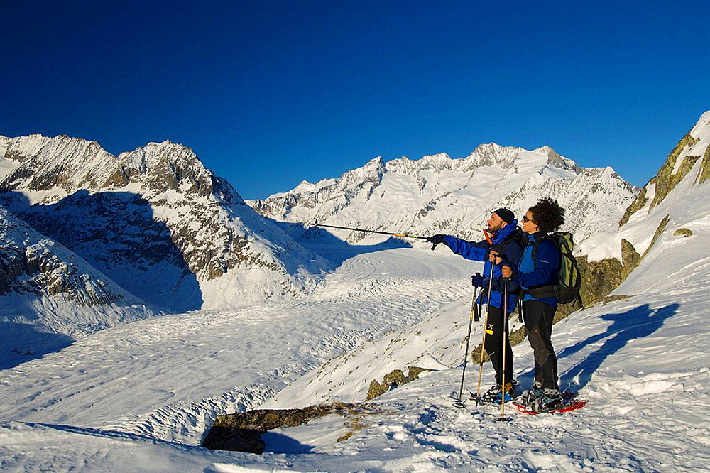 a couple of hikers walking with snowshoes in bettmerhorn with the aletsch glacier in the background bettmeralp municipality raron district valais canton switzerland europe