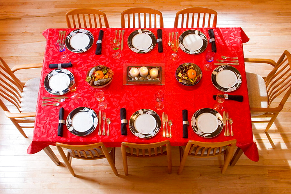 Aerial view of a dining room table set for Thanksgiving dinner, with red tablecloth, formal china, candles, and harvest centerpieces