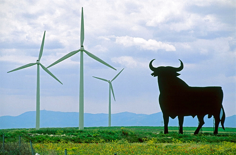 Bull silhouette, typical advertising of Spanish sherry Osborne, and wind turbines by windfarm, Zaragoza province, Aragon, Spain - 817-163111
