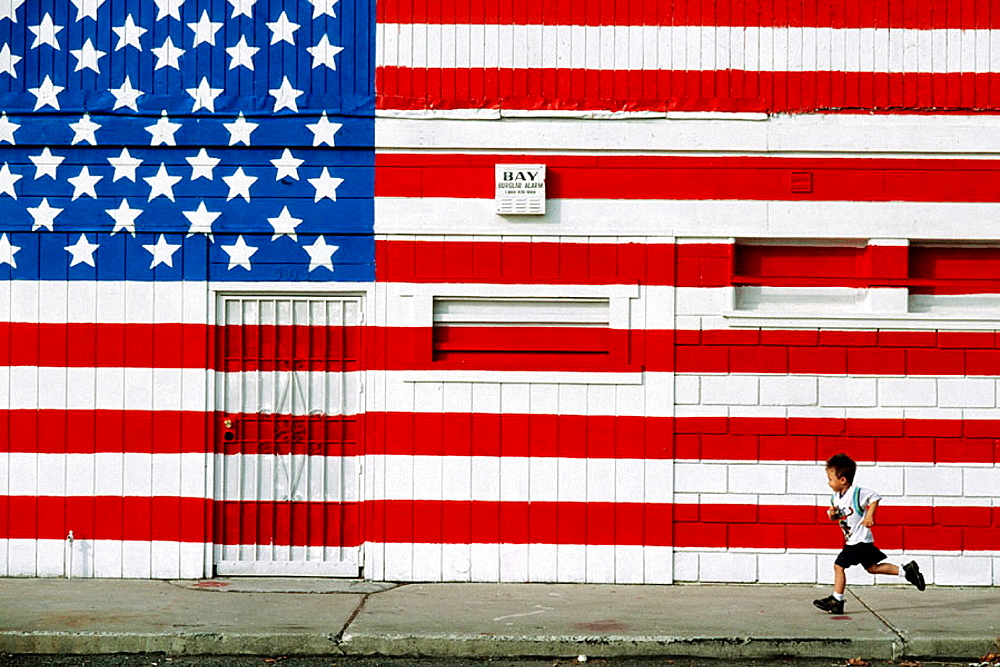 Child running in front of US flag painted on wall, California, USA