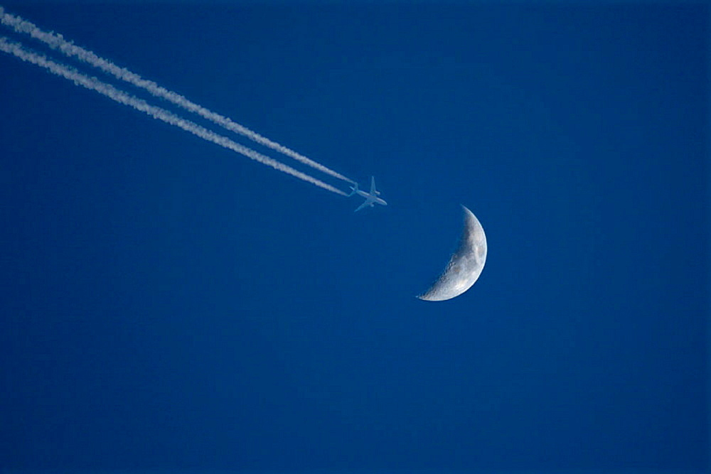 Flying plane just passing ower the moon.