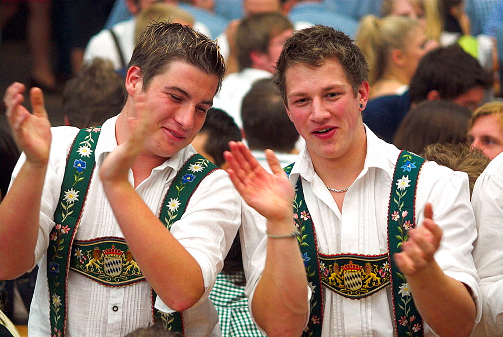 Young men with traditional Bavarian costume at Oktoberfest beer tent, Munich, Bavaria, Germany - 817-175522