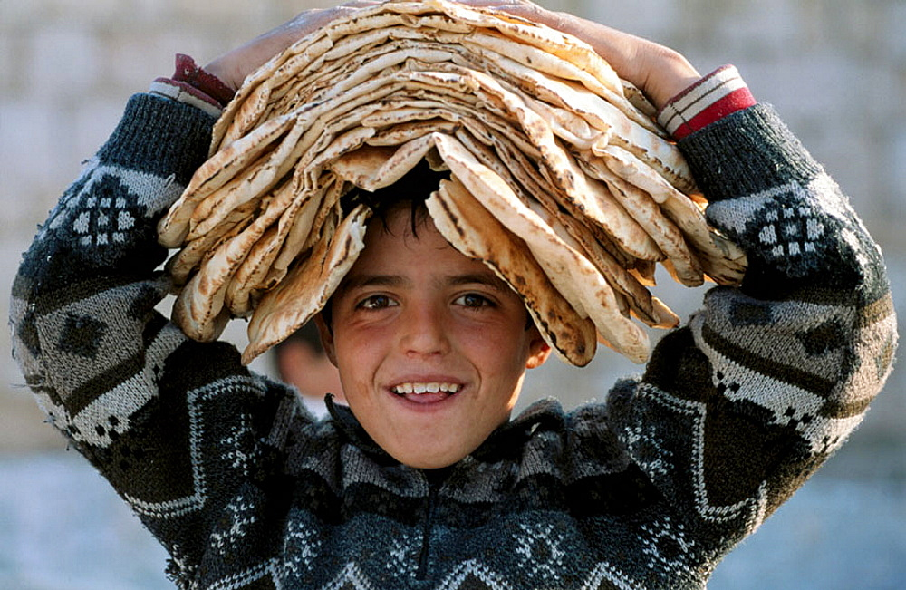 Boy wearing breads on his head, Maaloula christian village, Syria