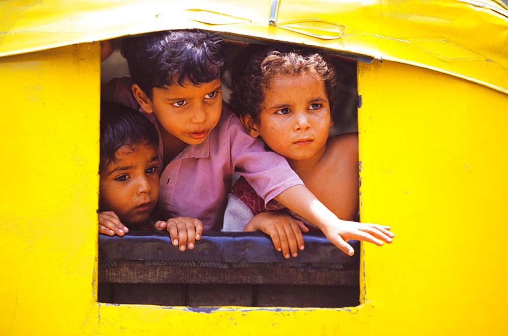 Children playing in a rickshaw, New Delhi, India