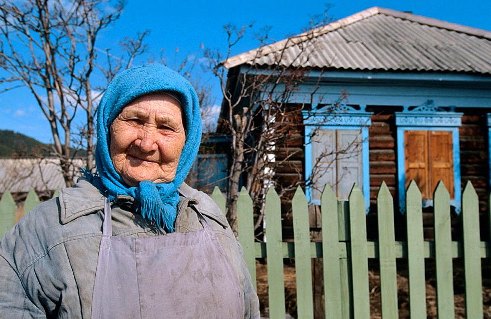Woman in front of wooden house, Rougir village, Olhkon Island, Baikal lake, Siberia, Russia
