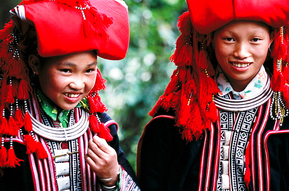 Ethnic Red Dao girls commonly wear elaborate red headdresses sometimes embellished with silver and pom poms, Sapa, Lao Cai province, Vietnam.