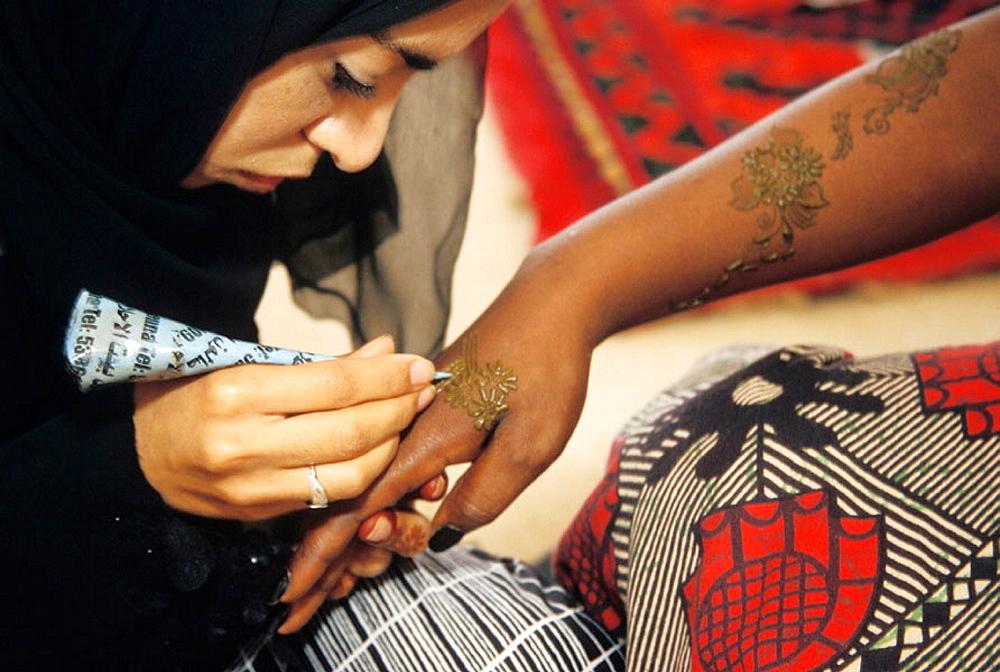 Woman doing henna tattoo, Dubai, UAE
