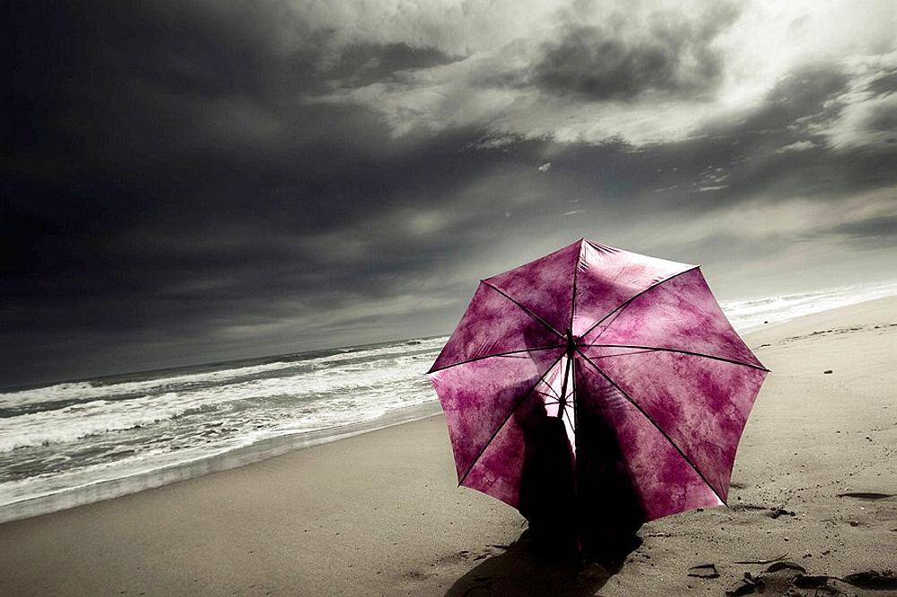 Mujer con paraguas sentada en la playa tras la tormenta.