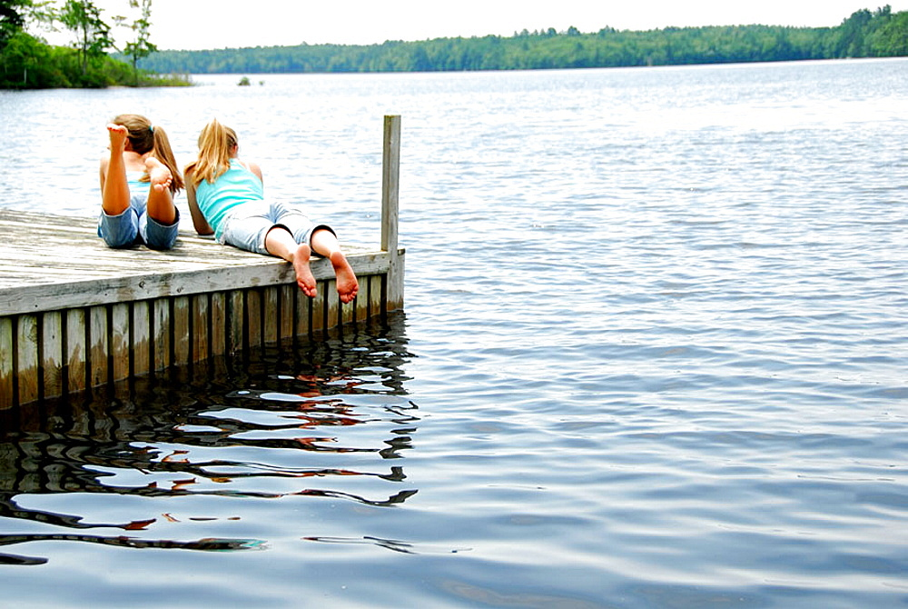 girl 13 with girl 18 together on dock looking out at lake