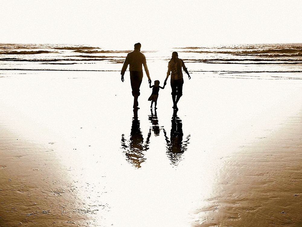 A husband and wife, holding the hands of their baby girl, helping her walk with them through the ocean surf