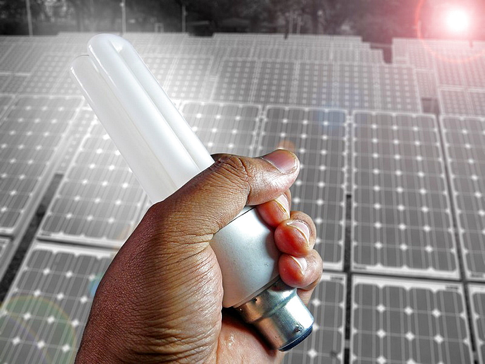 CFL Light in Human Hand in front of Solar panels