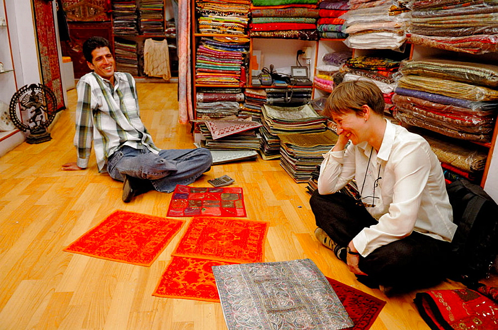 German female tourist negotiating prices for typical indian fabrics in a small boutique in the jewish part of Cochin (Kochi), Cochin, Kerala, India 2005
