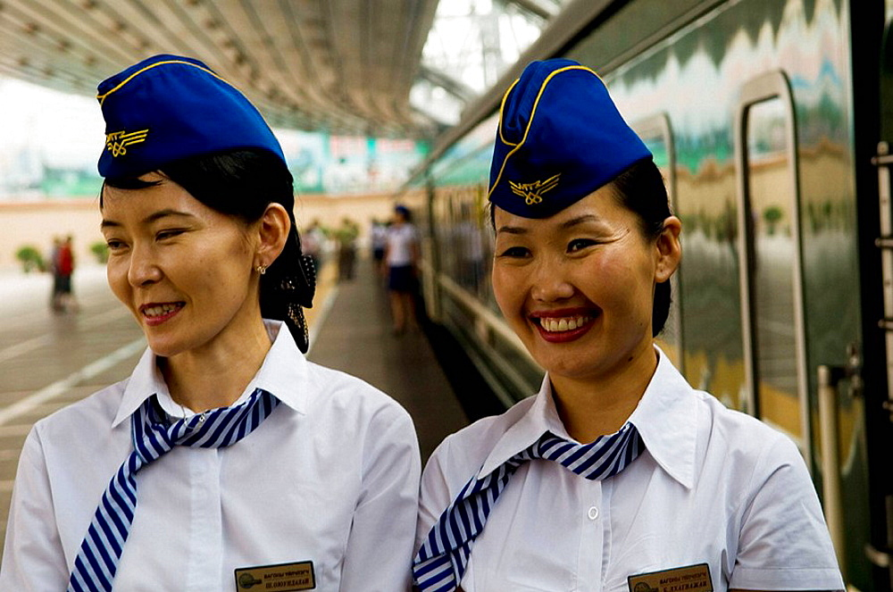 Mongolian ticket conducters stand by their train - Beijing Railway station, China