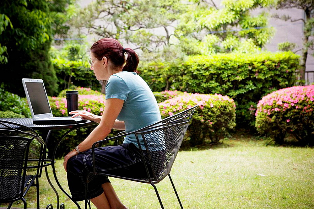 A woman sitting in front of a lap top computer outside
